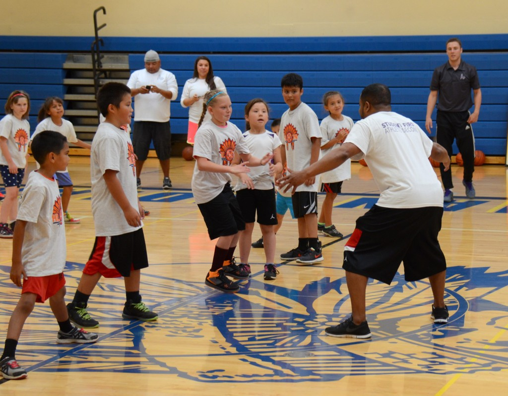 Coach Lee Adams demonstrates defense as youngsters and other coaches look on. (Jack McNeel)